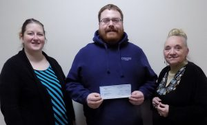 Alex Schoonover, Site Manager, Timberwolf Farms, LLC, Pipestone Systems presents $1000 donation to the Chamber for sign.